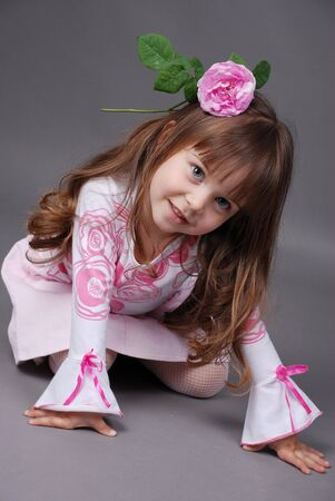 pretty little girl with pink rose in her hair