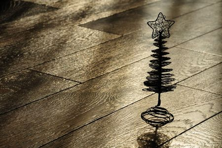 silhouette of the christmas tree on a dark wooden floor
