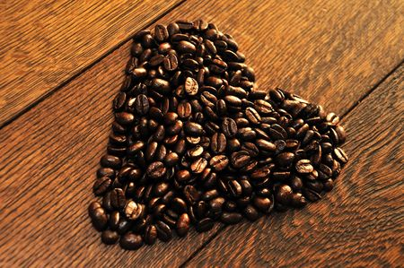 heart made of coffee beans on a wooden floor