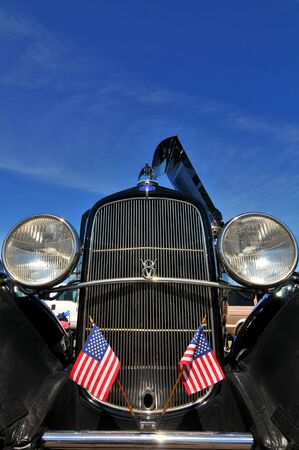 black vintage car with american flags on the hood on blue sky Editorial
