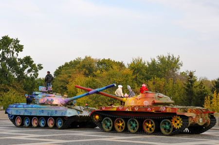 military tank painted in colorful flowers with children in Ukraine, Kiev, 2010 Editorial