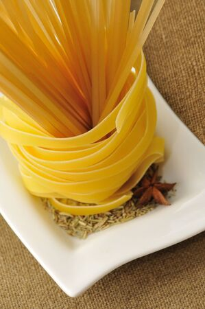 tagliatelle pasta and spaghetti with rosemary on white plate photo