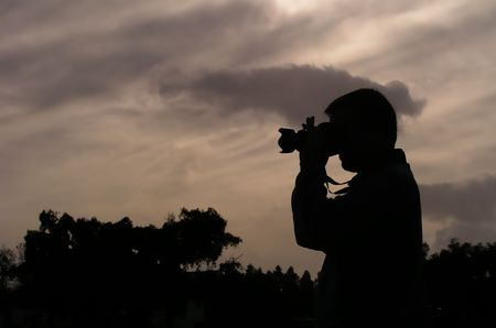 silhouette of a photographer in a brown sky