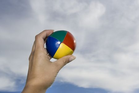 hand with coloured ball in a blue cloudy sky as a background