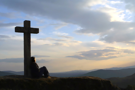 girl in the mountain in the sunset, contemplating the nature near a cross