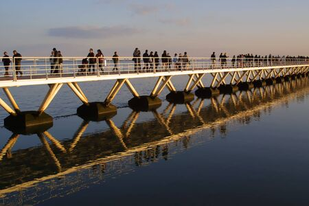 people crossing bridge with beautiful reflections in water photo