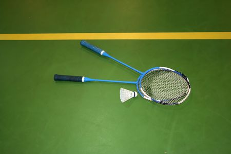 two badminton rackets in the green floor of the gym Stock Photo