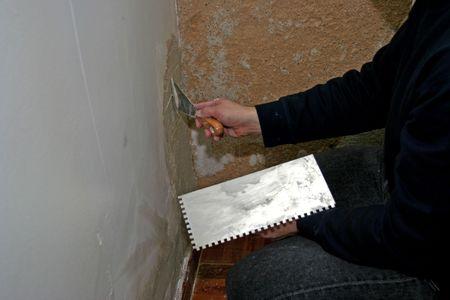 man reparing an old wall photo