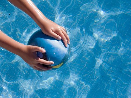 child holding a ball in the water of the pool Stock Photo