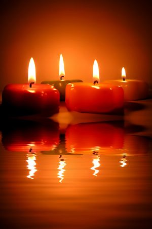 unwind:  candles and reflection in water