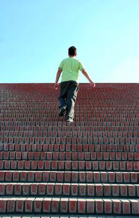subiendo escaleras: muchacho de escalada por las escaleras - s�mbolo de �xito  Foto de archivo