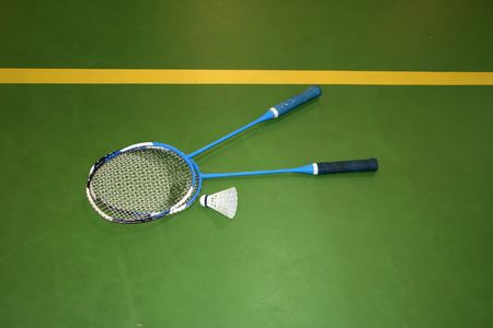 two badminton rackets in the green floor of the gym Stock Photo - 2854134