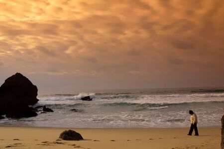 boy walking in the beach in the sunset in winter photo