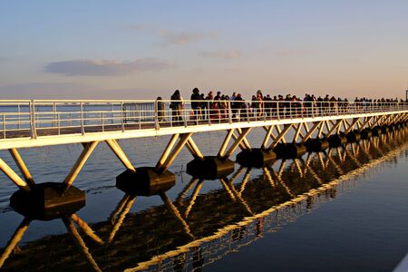 people crossing bridge with beautiful reflections in water - editorial use photo
