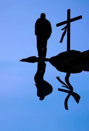 silhouette of man and cross and reflection in water in blue background Stock Photo