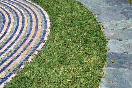 way in grass between blue tiles and granite way