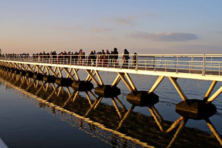 people crossing bridge with beautiful reflections in water - editorial use Stock Photo