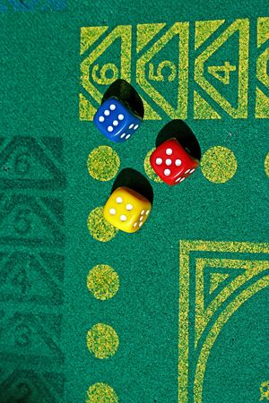 tree dice with number four, five and six in green game table photo