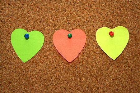 three empty heart notes in cork board