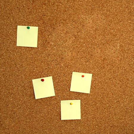square cork board with four empty yellow notes photo