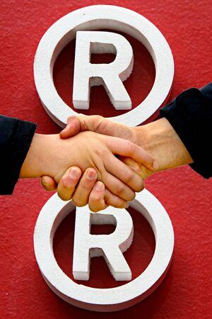 registered: shaking hands - registered trademark symbol in background