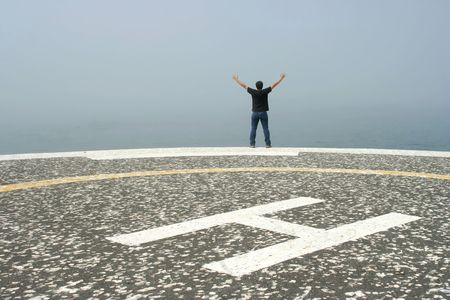 young man with arms open contemplating the ocean in foggy day\ in the heliport