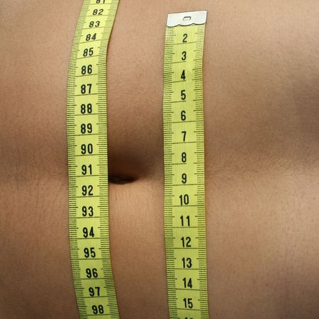 fitness symbols - woman belly with yellow tape measure