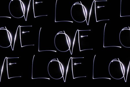 word love drawn with a lantern light in a black wall