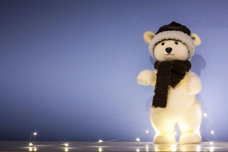 Blue Christmas background, with polar bear puppet, string lights, with copy space.