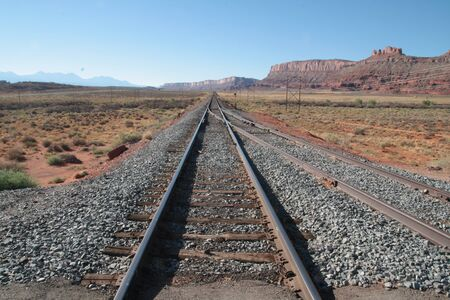 Railway section in Colorado desert, USA. Leads to nowhere, central perspective with horizon. Landscape background or wallpaper.