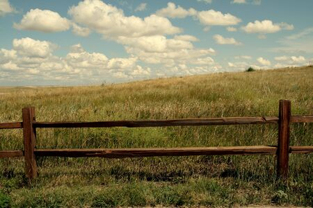 Natural Background with prairie beyond fence and blue sky.