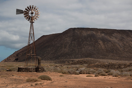 Windmill in arid mountain landscape, Lanzarote, Spain. Background or wallpaper. Ecology, wind power or renewable concept. Archivio Fotografico