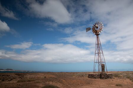 Windmill, Lanzarote, Spain. Ecology concept wallpaper background, with copyspace in blue sky.