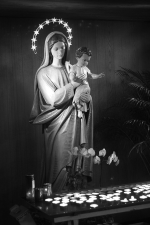 Mary and baby Jesus statue with votive candles. Religion catholic icon. Black and white, vertical shot.