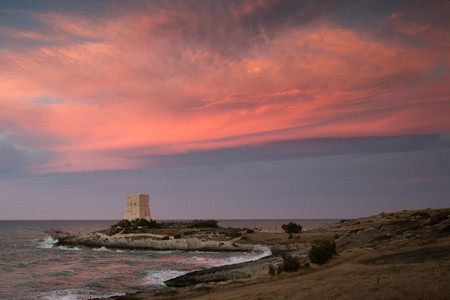 Landscape or seascape with pink sunset and an old defense tower on the sea. Vieste, italy. Stock Photo