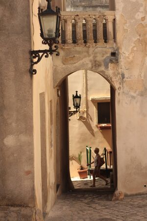 Otranto old town center. Picturesque alley with covered passage.