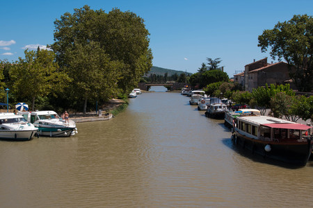View of Canal du Midi in the charming village of Homps on a sunny day.
