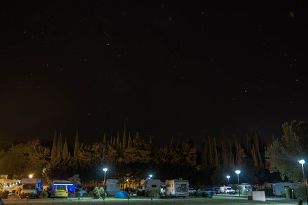 view of a campground at night with tents, campers, rv, and a big space for copyspace. Reklamní fotografie