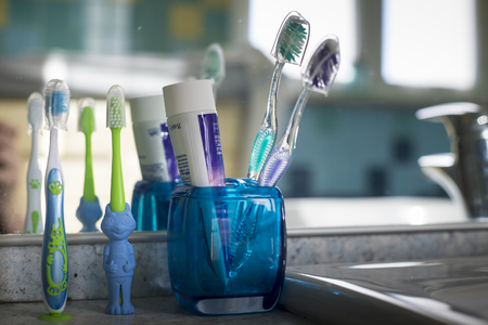Family toothbrushes in bathroom, with two normal ones and an animal shaped children toothbrush Imagens