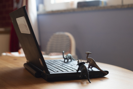 Open laptop on wooden table with small dinosaur toys that seem looking at the screen. Natural light.