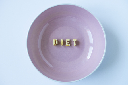 """le mot """"régime"""" écrit avec des pâtes dans un plat rose"""