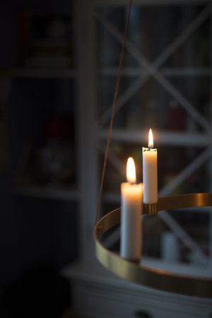 Winter, christmas or hygge background with candles glowing on a golden advent chandelier. Vertical shot with copy space. Stock Photo