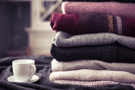 Pile of colorful sweaters with hot drink white cup on the side, background with copy space, cozy hygge wallpaper. Pink filter.