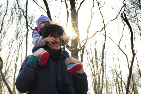 Young dad carrying baby on his shoulders in a forest. Baby covering her dad's eyes for fun. 版權商用圖片