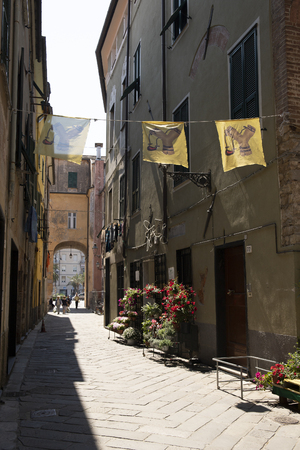 View of an old street in the Slingshot district of Albenga town, Liguria, Italy. The emblem of the slingback is on the flags over the street. Vertical shot.