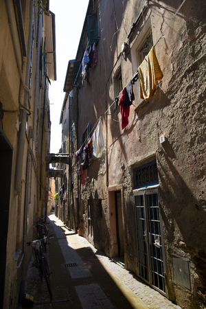 Vista de la calle del casco antiguo de Albenga, con tendedero. Liguria, Italia.