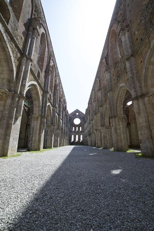 The central nave of San Galgano Abbey on a sunny day. Tuscany, Italy. Vertical shot.