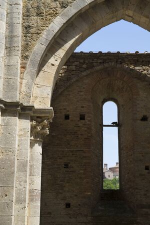 Detail of an arch in San Galgano abbey with a window view of the nearest buildings. Vertical shot.