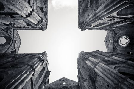 Bottom up view of San Galgano abbey with the cross shape in the sky. Tuscany, Italy. Black and white.