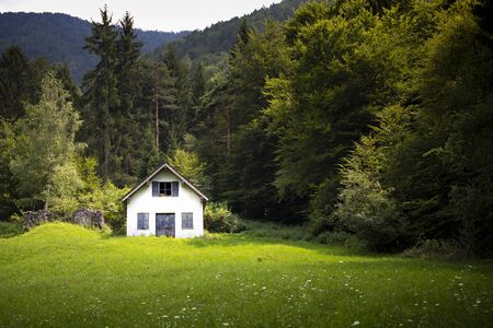 Green mountain summer landscape with an isolated white cabin or barn across the meadow. Solitude and tranquility background or wallpaper with right copy space. Banco de Imagens